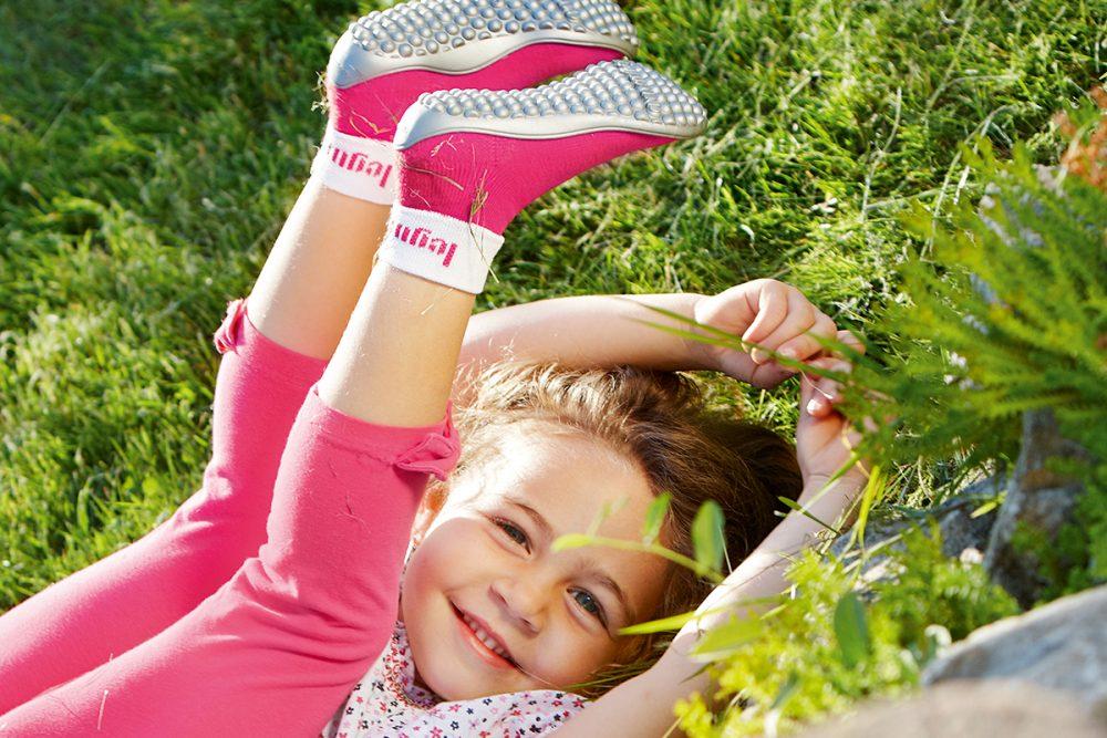 Mädchen mit Leguano Schuhen auf der Wiese